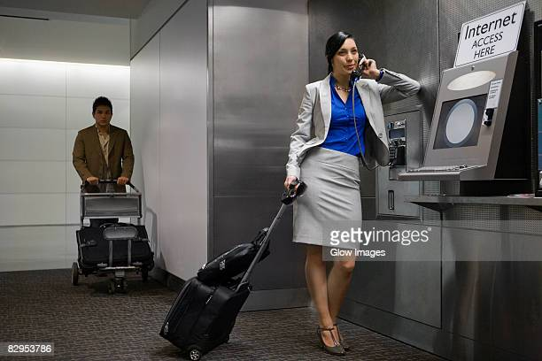 Businesswoman talking on a pay phone with a businessman standing behind her at an airport