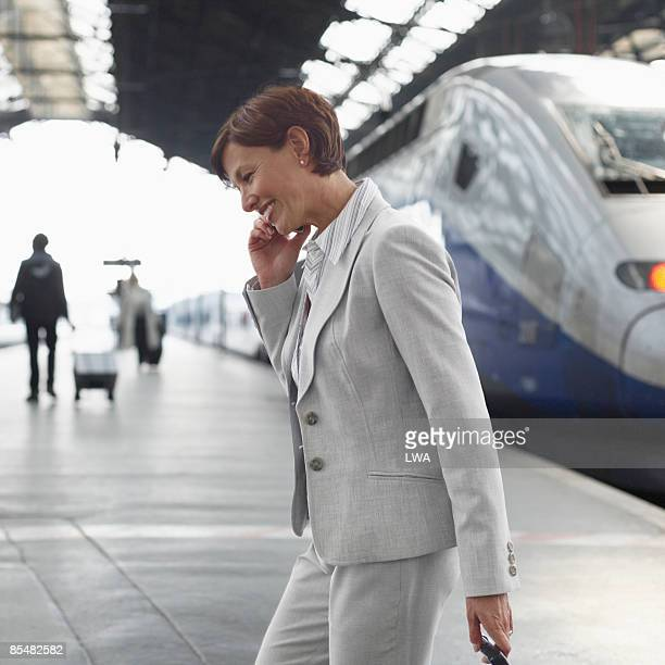 businesswoman talking on cell in train station - gare du nord stock pictures, royalty-free photos & images