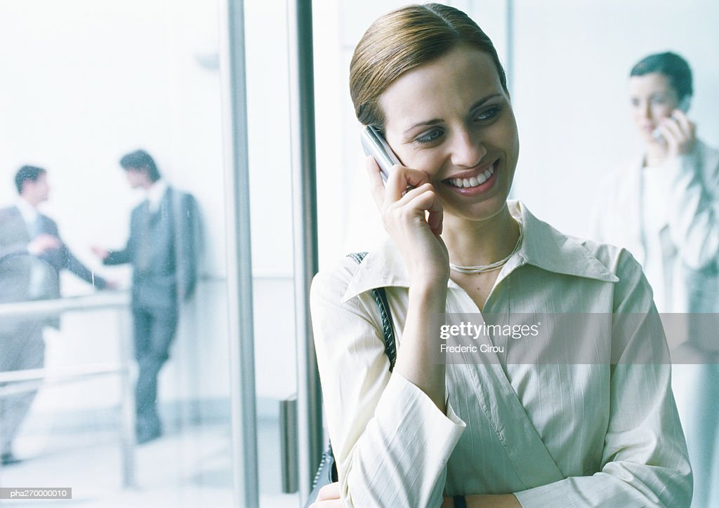 Businesswoman talking on cell phone, businesspeople in background : Stockfoto
