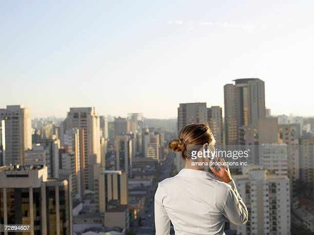 Businesswoman talking on cell phone, city in background (rear view), Sao Paolo, Brazil
