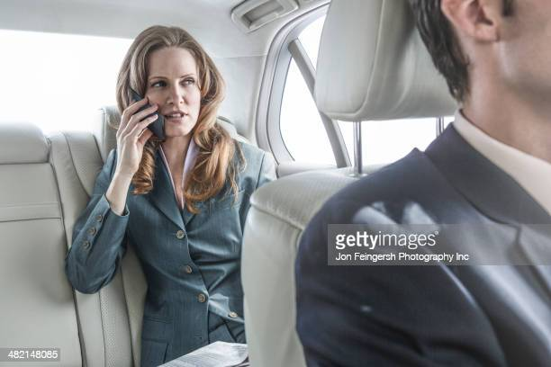 Businesswoman talking on cell phone in car