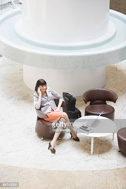 Businesswoman talking on cell phone in hotel lobby