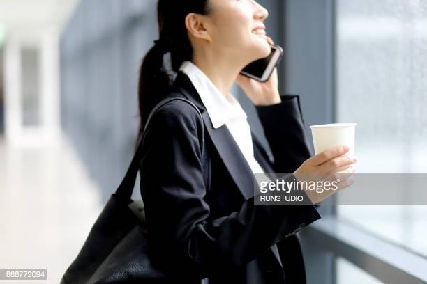 Businesswoman talking on cell phone in office corridor window