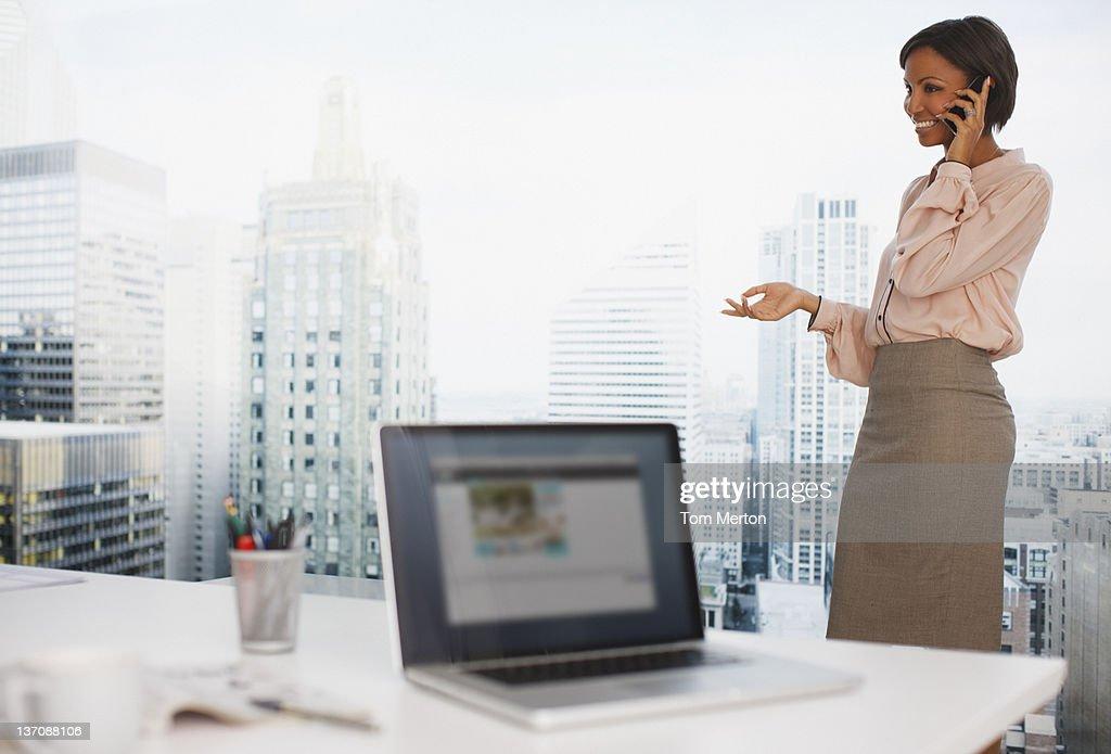 携帯電話で話しているビジネスウーマンにオフィス : ストックフォト