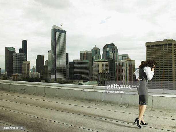 Businesswoman talking on cell phone on rooftop in city, side view