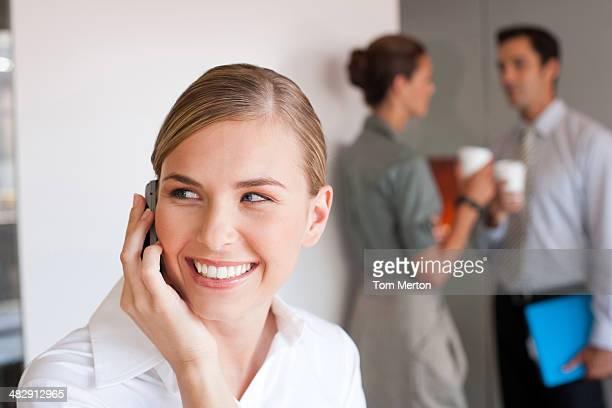 Femme d'affaires parler sur téléphone portable avec des collègues en arrière-plan