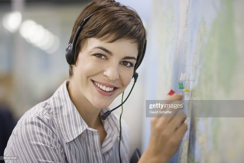 Businesswoman talking on headset in office and marking map : Stock Photo
