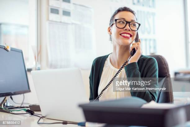 Businesswoman talking on landline phone in office