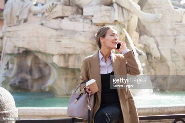 businesswoman talking on mobile phone, holding takeaway coffee in sustainable coffee cup - brown purse stock pictures, royalty-free photos & images