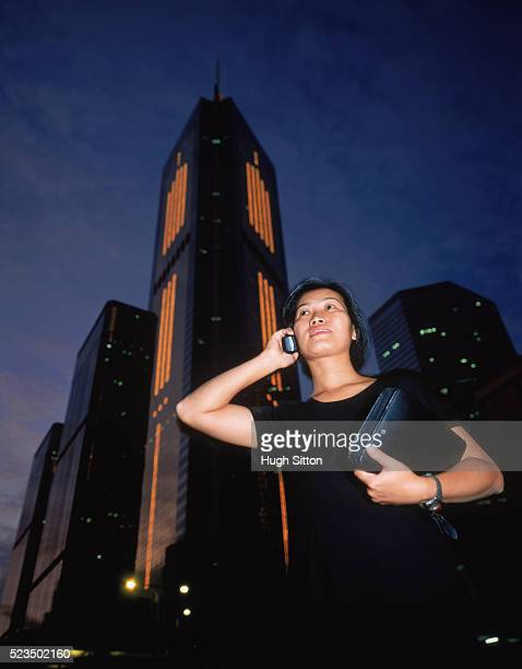 businesswoman talking on mobile phone in front of skyscrapers, hongkong, china - hugh sitton stock pictures, royalty-free photos & images