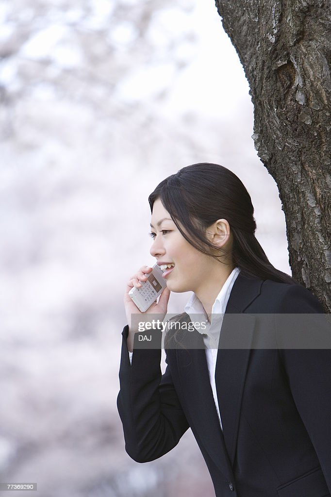 Businesswoman Talking on Mobile Phone, Waist Up, Side View, Differential Focus : Photo
