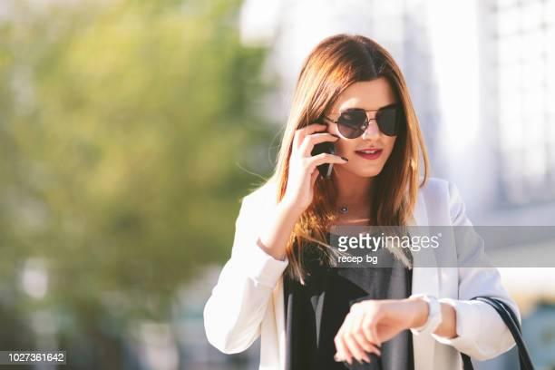empresária, falando no telefone e verificar o tempo - ver a hora - fotografias e filmes do acervo