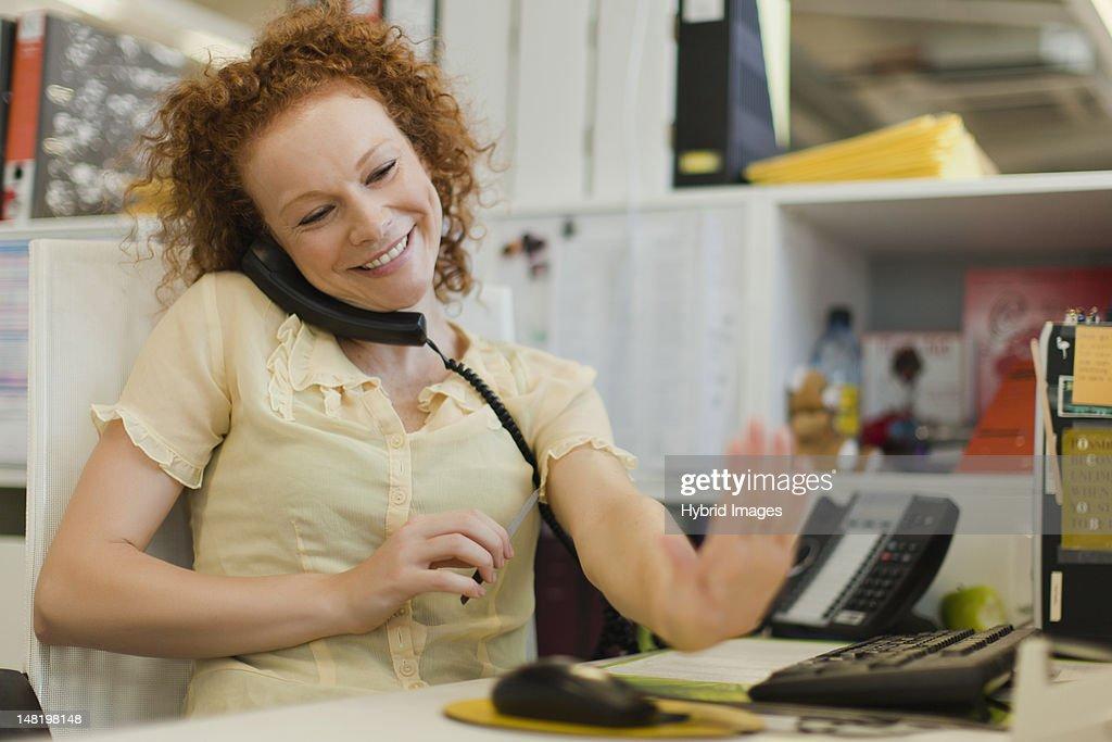 Businesswoman talking on phone at desk : Stock Photo