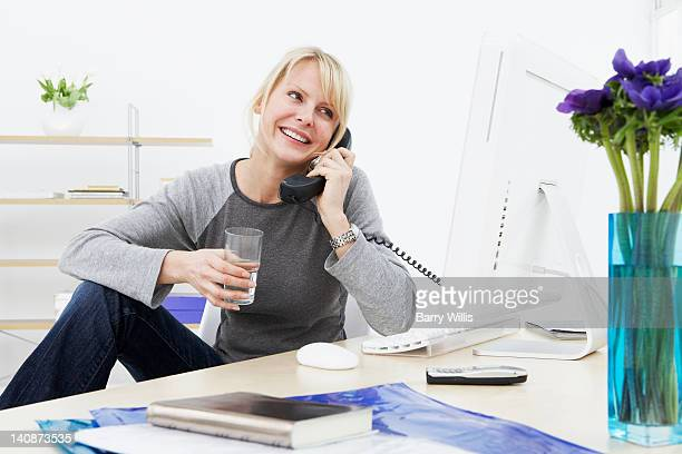 Businesswoman talking on phone at work