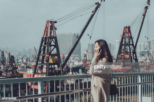 Businesswoman talking on phone in city, standing against busy container terminal port