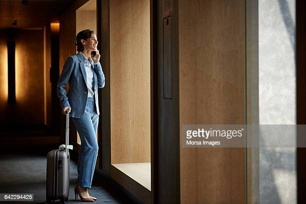 businesswoman talking on phone in hotel corridor - geschäftsreise stock-fotos und bilder