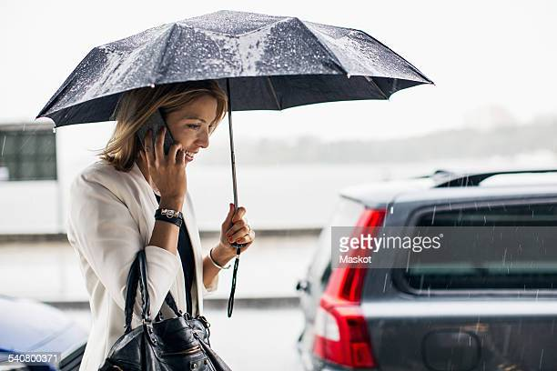 Businesswoman talking on smart phone during rainy season in city
