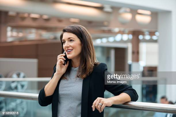 businesswoman talking on smart phone in office - smart casual stock pictures, royalty-free photos & images