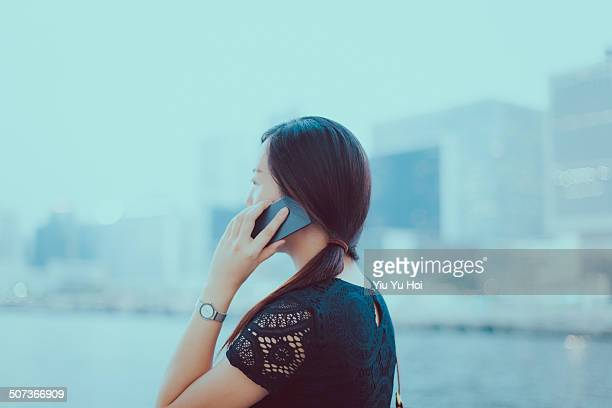 businesswoman talking on smartphone by the harbour - yiu yu hoi stock pictures, royalty-free photos & images