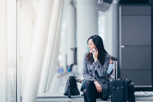 Businesswoman talking on smartphone in airport - gettyimageskorea