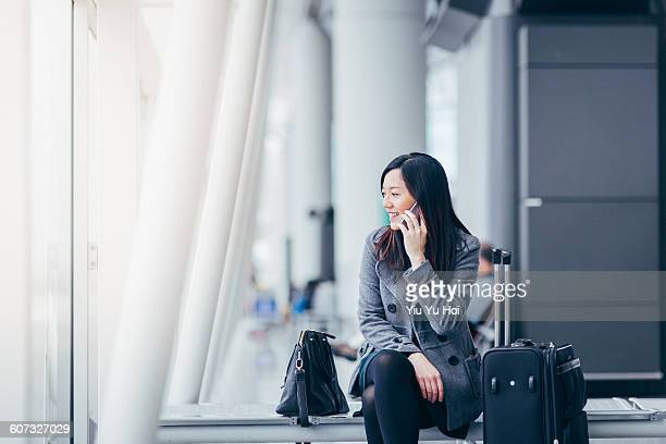 Businesswoman talking on smartphone in airport