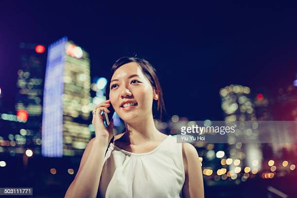 businesswoman talking on smartphone in city street - yiu yu hoi stock pictures, royalty-free photos & images