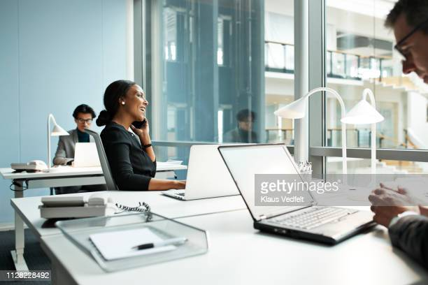 businesswoman talking on smartphone in open office - hot desking stock pictures, royalty-free photos & images