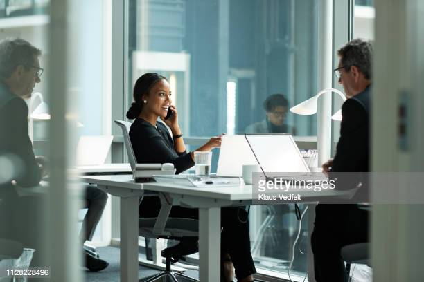 businesswoman talking on smartphone in open office - flexplekken stockfoto's en -beelden