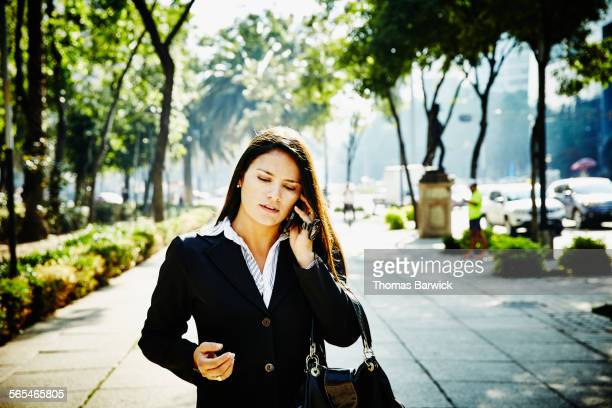 Businesswoman talking on smartphone on sidewalk