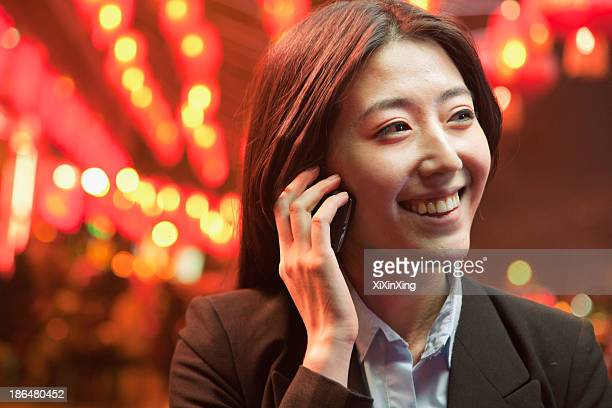 Businesswoman talking on the smart phone, night street, red lanterns on the background