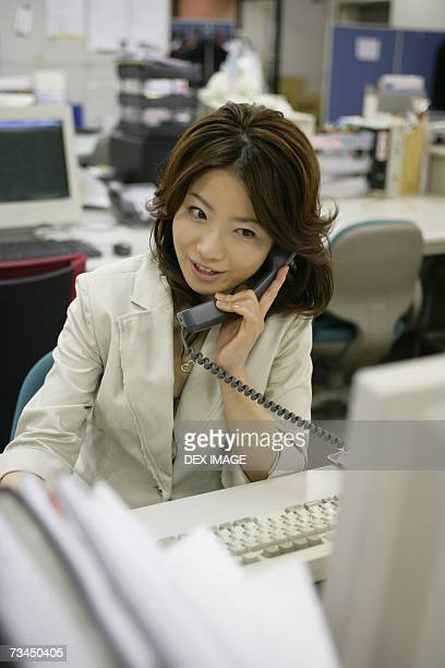 Businesswoman talking on the telephone and using a computer