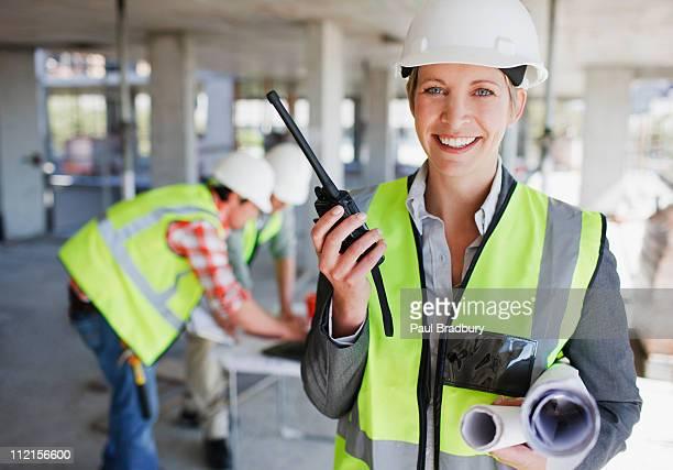 Mulher de Negócios fala no walkie talkie no local de Construção