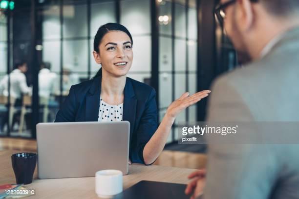imprenditrice che parla con un collega - candidato foto e immagini stock