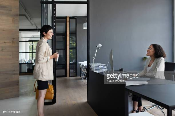 businesswoman talking to colleague in office - cream coloured blazer stock pictures, royalty-free photos & images