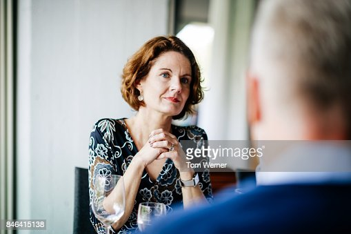 Businesswoman Talking To Colleagues Over Lunch In Restaurant.