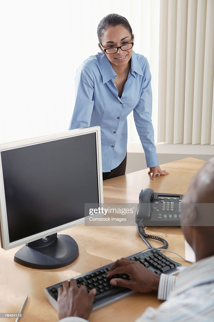 Businesswoman talking to co-worker at desk : Stockfoto