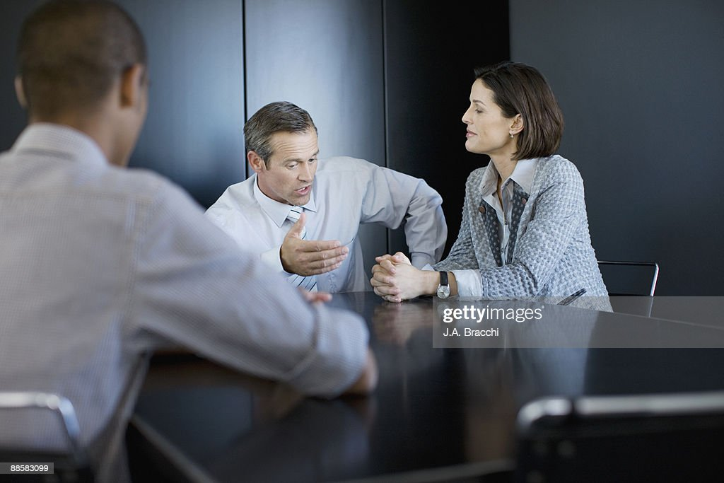 Businesswoman talking to co-workers in conference room : Stock Photo