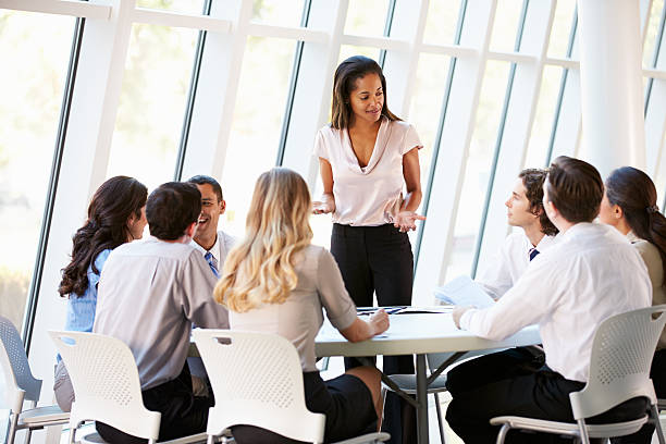 Businesswoman talking to group of executives