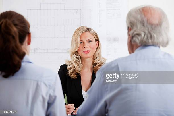 Businesswoman talking to man and woman