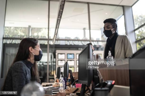 onderneemster die aan receptioniste bij ingang van de lobby van het bureau spreekt - met gezichtsmasker - opening event stockfoto's en -beelden