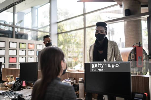 businesswoman talking to receptionist on entrance of office's lobby - with face mask - arrival stock pictures, royalty-free photos & images