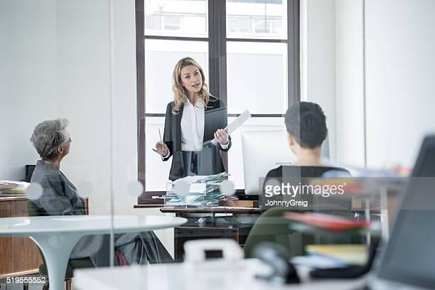 Geschäftsfrau Gespräch mit zwei weiblichen Kollegen im Meetingraum
