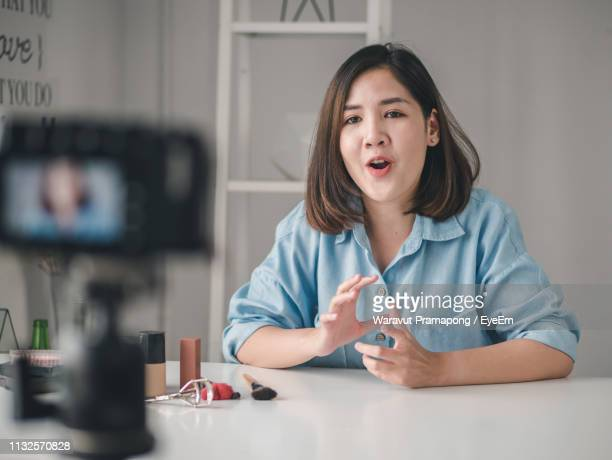 businesswoman talking while looking at camera in office - frontaal stockfoto's en -beelden