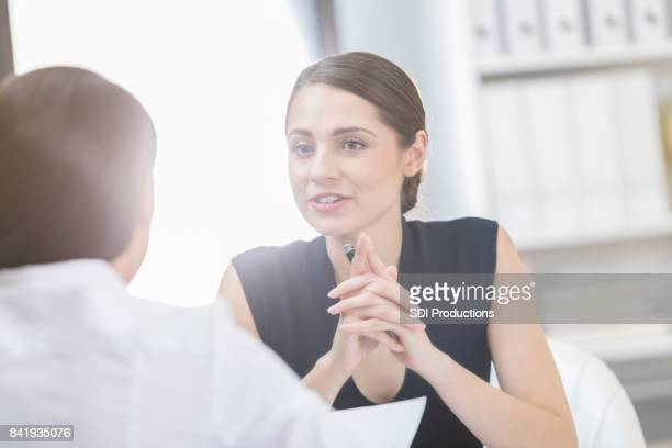 Businesswoman talks with colleague in her office