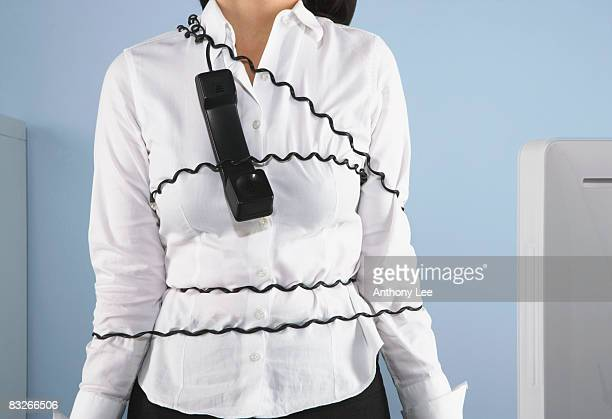 Businesswoman tangled up in telephone cord