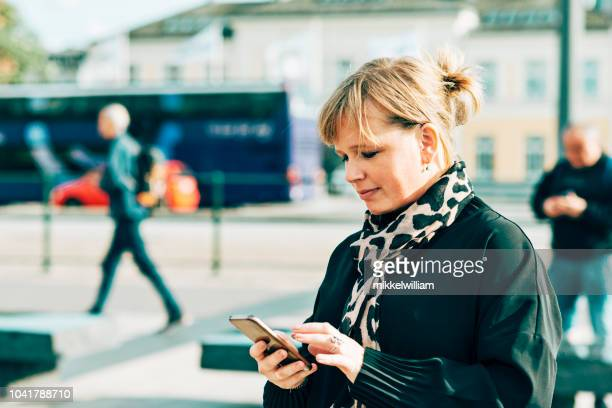 Businesswoman taps the screen of her mobile phone while walking outside
