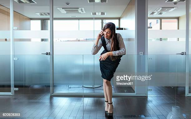 Businesswoman telephoning with smartphone at corridor of an office