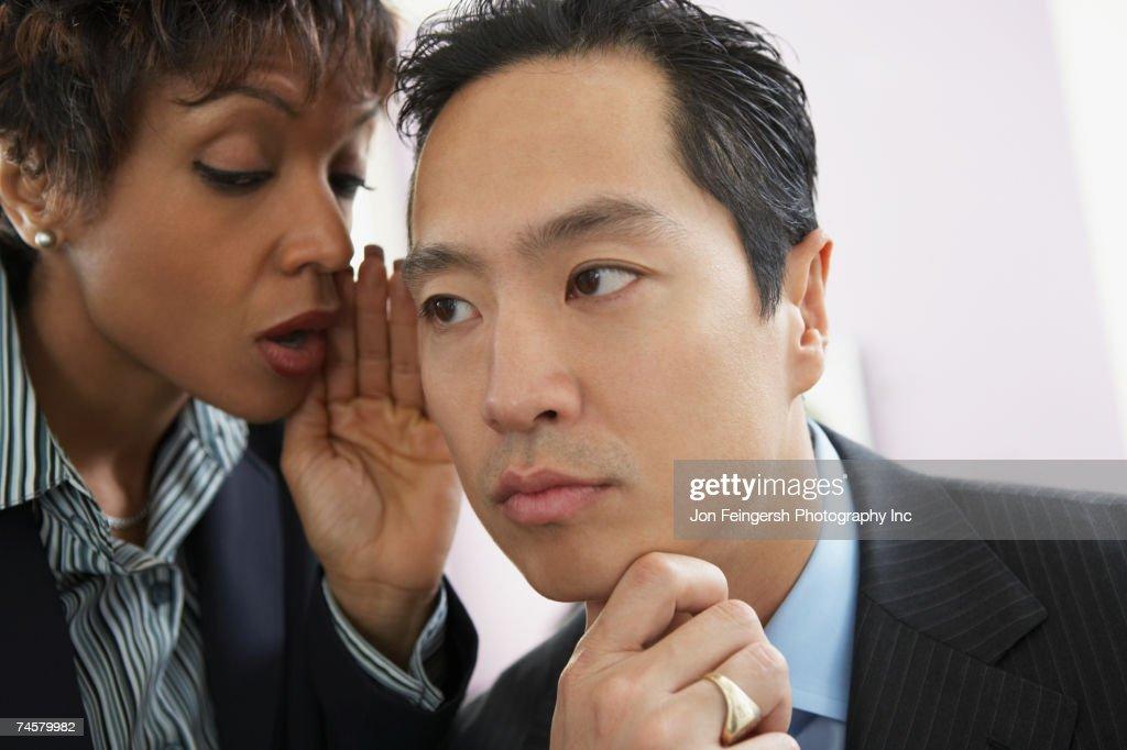 Businesswoman telling secret to businessman : Stock Photo