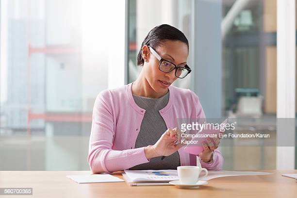 businesswoman text messaging in conference room - オールバック ストックフォトと画像