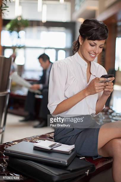 Businesswoman text messaging on cell phone in hotel lobby